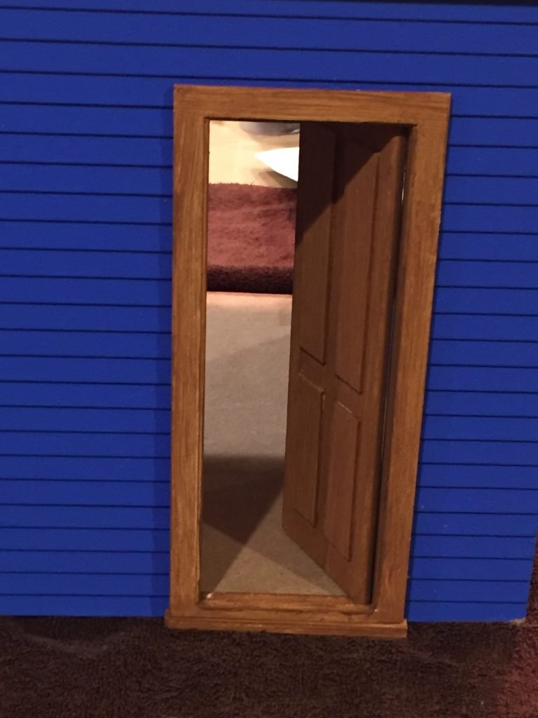 A close up of the door in the dollhouse