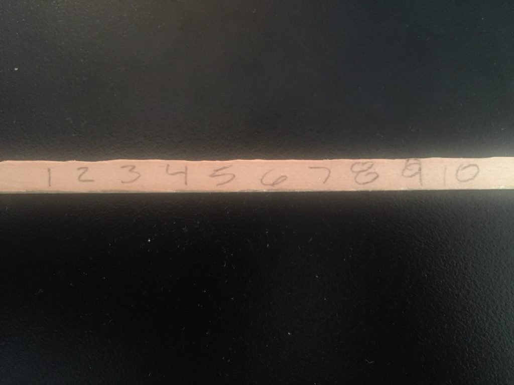 A picture of a plain balsa wood stick with the numbers 1 thru 10 on it in pencil