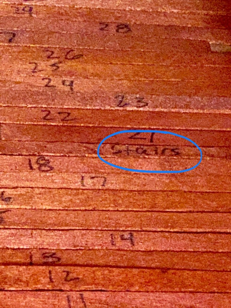 "A picture of a floor board with the word ""stairs"" on it, instead of a number"