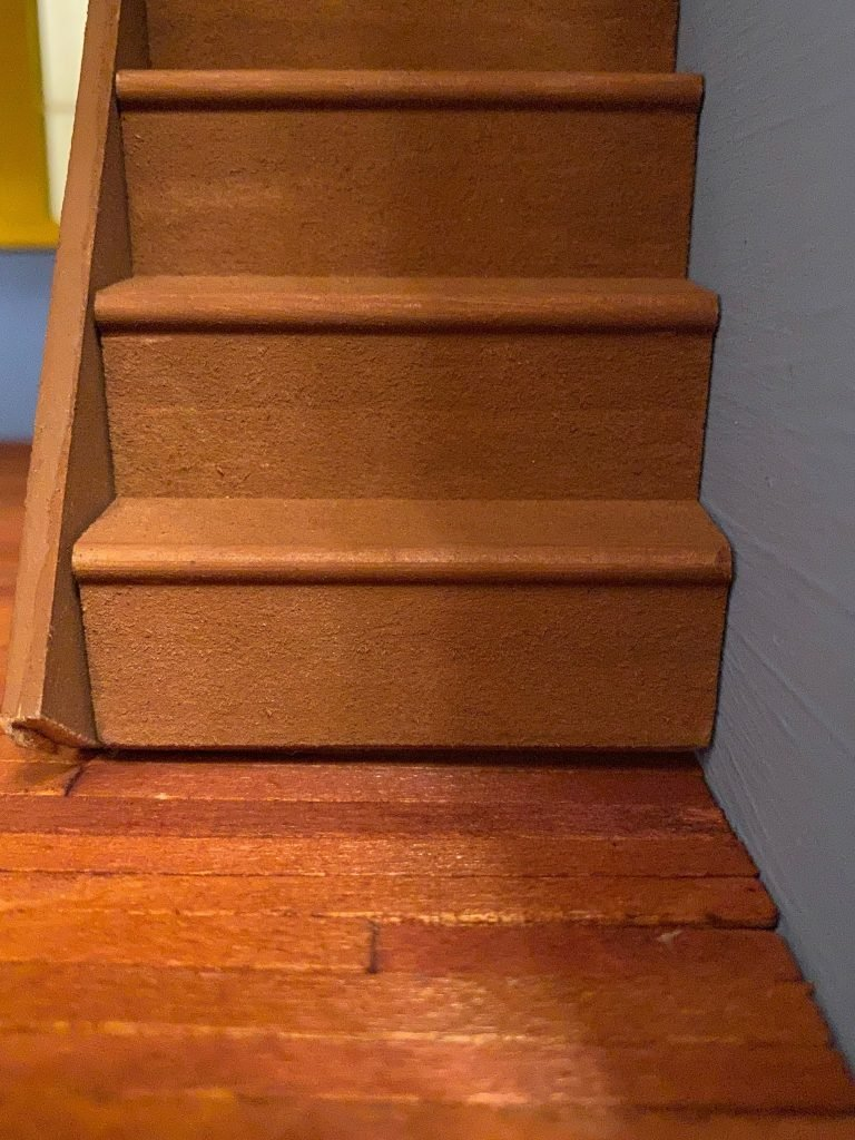 A front view of the bottom of the stairs on the floor. The bottom of the staircase is not flush against the wood.