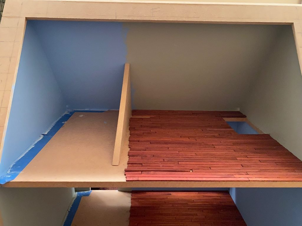 The second floor of the dollhouse with the wood floors and wall in place but no tile floor