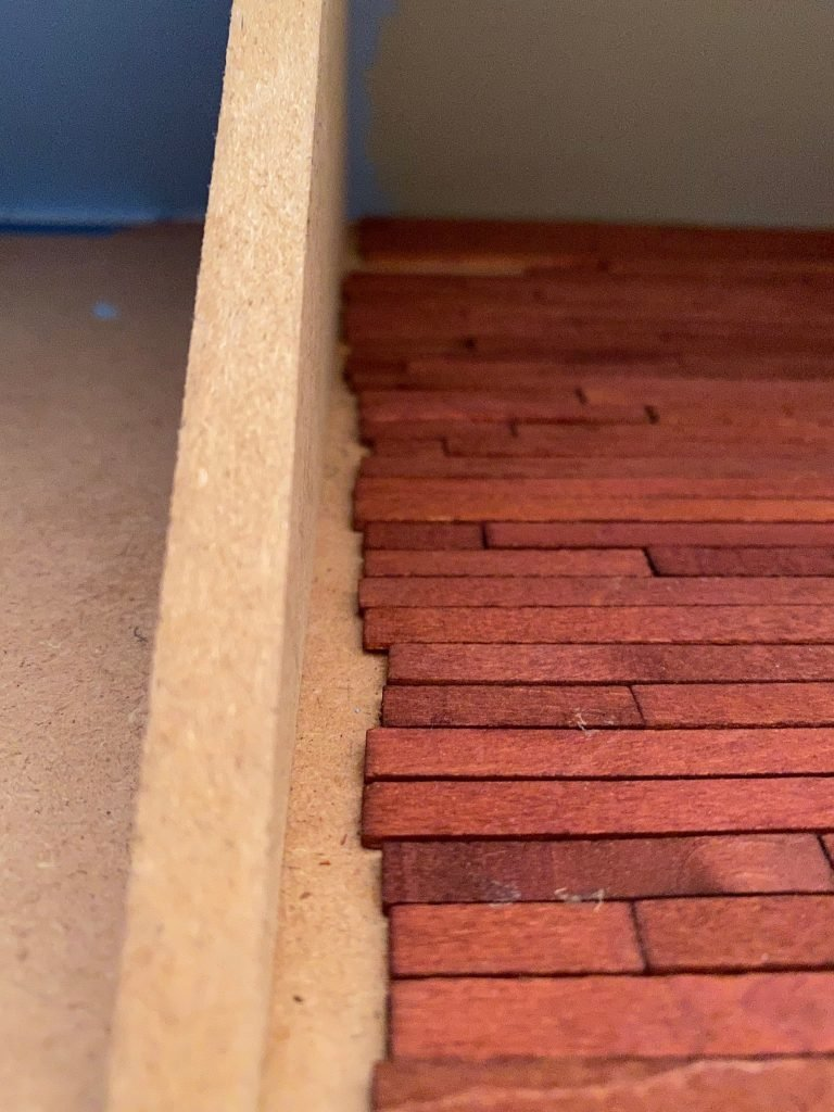 A close up of the uneven ends of the floorboards