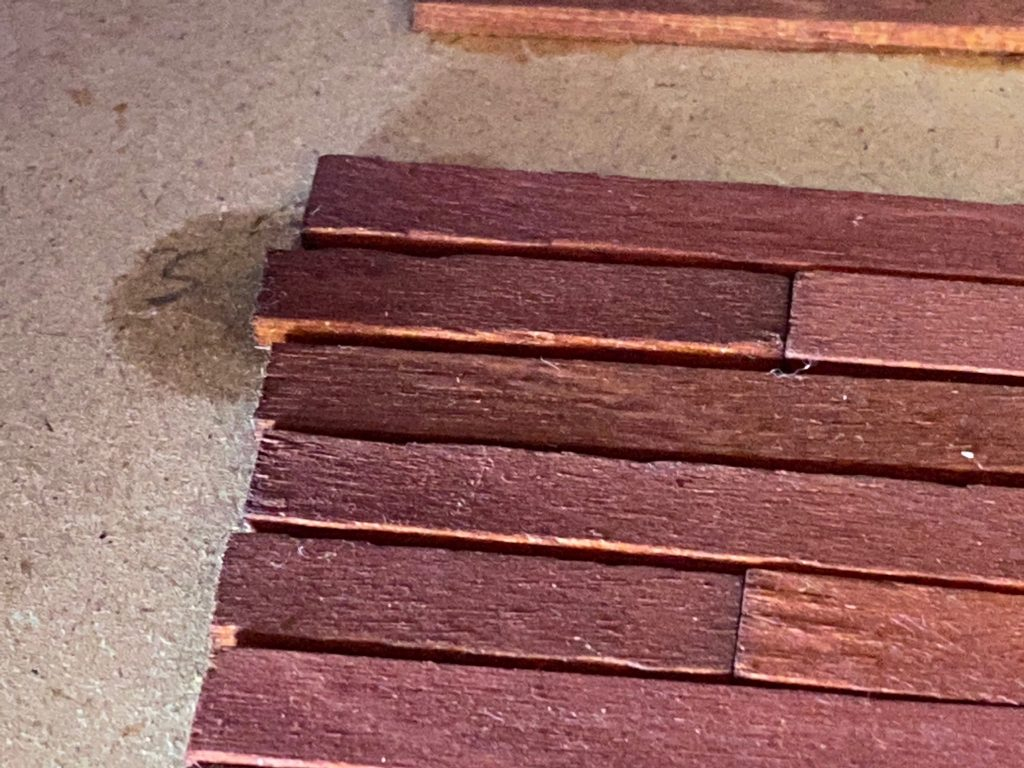 A close up of the stained floor after I tried ungluing the floorboards