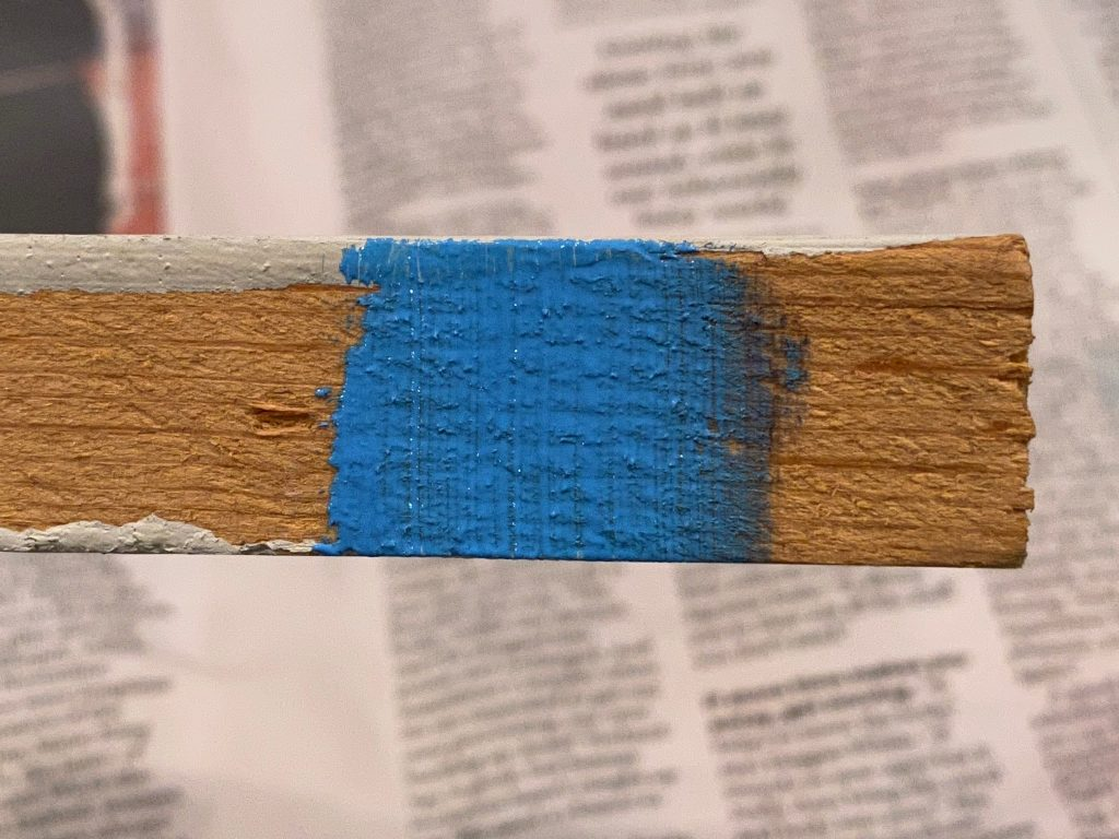 The acrylic paint on the unfinished side of the wood